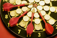 Coins and Darts on Dart Board Stock Photography
