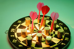 Coins and Darts on Dart Board Royalty Free Stock Photo