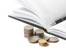 Coins, diary and pen Royalty Free Stock Photos