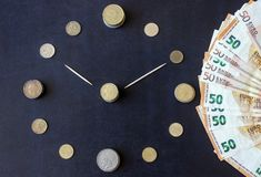 Coins of different countries are laid out in the shape of a clock face. Paper euro banknotes are located around. Time is money. stock images