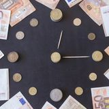Coins of different countries are laid out in the shape of a clock face. Paper euro banknotes are located around. Time is money. royalty free stock images
