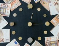 Coins of different countries are laid out in the shape of a clock face. Paper euro banknotes are located around. Time is money. stock photography
