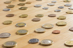 Coins from different countries on a wooden background Stock Images