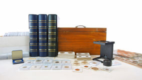 Coins of different countries of the world on white table with folders and supplies background Royalty Free Stock Photo