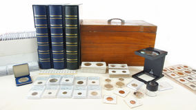 Coins of different countries of the world on white table with folders and supplies background Royalty Free Stock Images