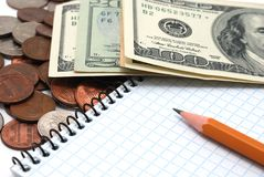 Coins, dollar bills, notebook and pencil. Royalty Free Stock Images