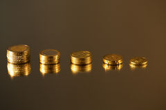 Coins Economy. On mirror background Stock Photos