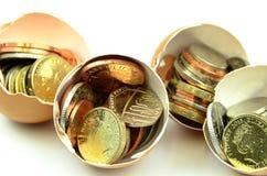 Coins in eggs Stock Photos