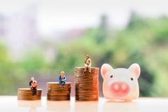 Coins and elderly people on nature background; money saving. stock photo