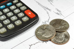 Coins with electronic calculator on the background of currency growth schedule royalty free stock photos