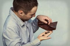 Coins and an empty wallet. Poor man pulls out the last coins from her purse stock photography