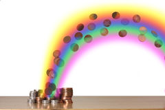Coins at the end of the rainbow. Rainbow with coins in, leading to a pile of coins royalty free stock images