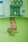 Coins with Euro. Coins with one hundred Euro bill on the paper Royalty Free Stock Photos