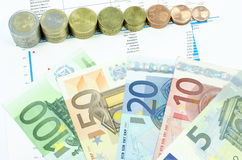 Coins and euro banknotes composition. Euro coins making a scale and 5, 10, 20, 50 and 100 euro banknotes composition with some figures and trends in the Stock Photography