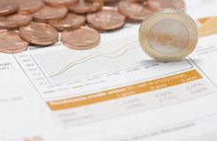 Coins, euro on edge and stock market graph Stock Photo