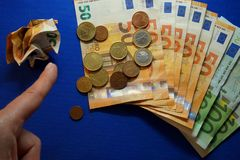 Several euro banknotes and coins with finger pointing stock photography