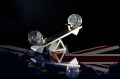 17.03 073 Coins of the euro and a pound on a wooden swing. The f stock photography