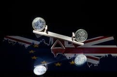 17.03 073 Coins of the euro and a pound on a wooden swing. The a. Coins of the euro and a pound on a wooden swing symbolizing the change of the course. Objects Stock Image