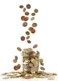 Coins falling into a jar Stock Photography