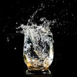 Coins falling splashing into a water glass stock photography