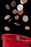 Coins falling into trash can. Several United States' coins falling into a red trash can, with a black background. The coins include pennies, dimes, quarters, and stock image