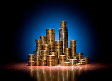 Coins folded on wooden desk as towers of the city Royalty Free Stock Image