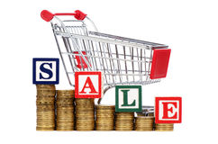 Coins in the form of the diagramme, shopping cart. And word SALE Royalty Free Stock Image