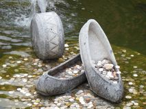 Coins in fountain with stone shoes stock photography