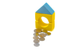 Coins in front of house made of building blocks. Royalty Free Stock Photography