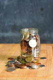 Coins in a full jar suggesting home savings Royalty Free Stock Image
