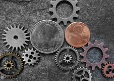 Coins and gears. Coins and metal gears on dark textured background Stock Photography