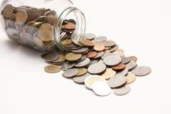 Coins in a glass bottle. Coins in a glass bottle on white Stock Photos