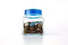 Coins In A Glass Bottle. With blue lid Stock Photos