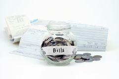 Coins in glass container with Bills label with bills receipts is. Olated on white background. Financial concept stock images