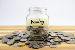 Coins and glass container with label on wooden surface Royalty Free Stock Photography