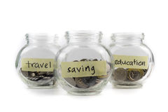 Coins in glass container with travel, saving and education labels Stock Photography