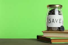 Coins in a glass jar and books Stock Images