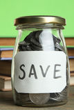 Coins in a glass jar and books Royalty Free Stock Photography