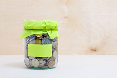 Coins in a glass jar Stock Photo