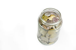 Coins in glass jar isolated on white background Stock Photos