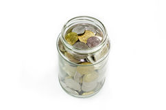 Coins in glass jar isolated on white background Stock Photo