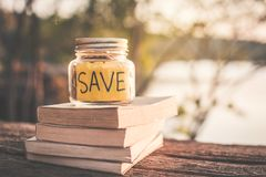 Coins on glass jar with save word and book on table in nature bokeh background. Color vintage style selective and soft focus ,concept saving for education Stock Photo