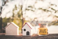 Coins on glass jar with save word and model house on table in nature bokeh background. Color vintage style selective and soft focus Stock Images