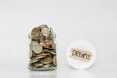 Coins in glass jar, saving money for following Dreams Stock Images
