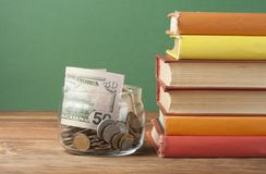 Coins in glass jar and stack of books on wooden table.Saving,financiai and education concept.