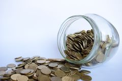 Close up coins in glass jar on white table. Coins scattered around. Isolated on white background. Saving concept. Coins in glass jar on white table. Coins royalty free stock images