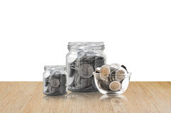 Coins in a glass jar on Wood floor ,savings coins - Investment And Interest Concept saving money concept, growing money on piggy b Royalty Free Stock Images