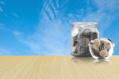Coins in a glass jar on Wood floor ,savings coins - Investment And Interest Concept saving money concept, growing money on piggy b Stock Images