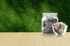 Coins in a glass jar on Wood floor ,savings coins - Investment And Interest Concept saving money concept, growing money on piggy b Stock Photography