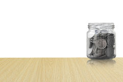 Coins in a glass jar on Wood floor ,savings coins - Investment And Interest Concept saving money concept Royalty Free Stock Image